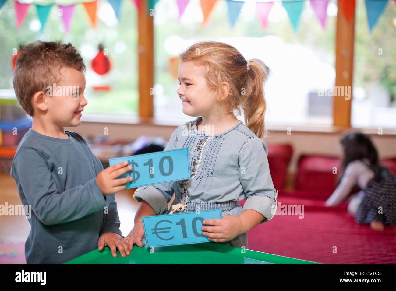 Garçon et fille euro comptage service à l'école maternelle Banque D'Images