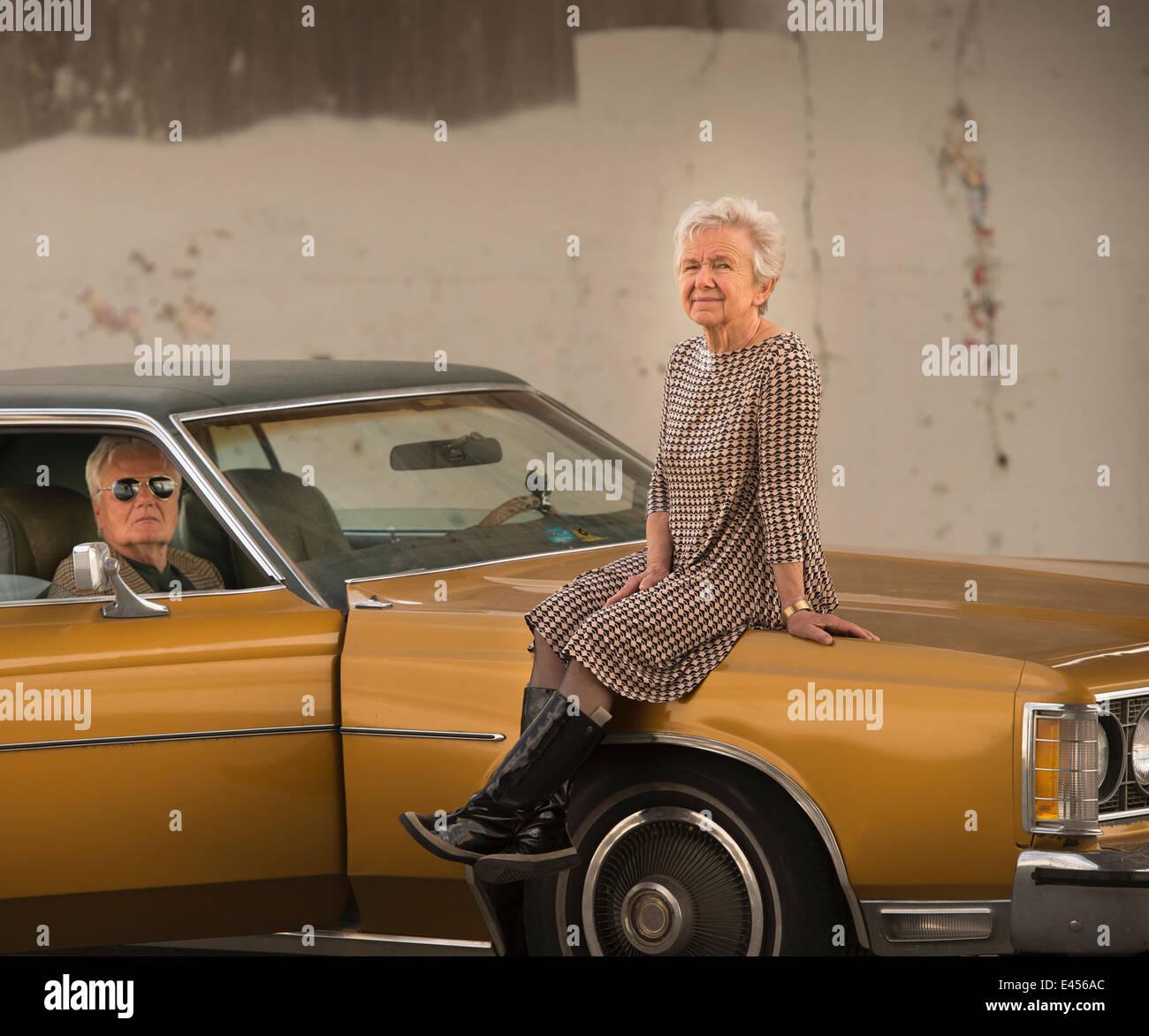 Portrait of senior woman cool sur capot de voiture classique maris Photo Stock