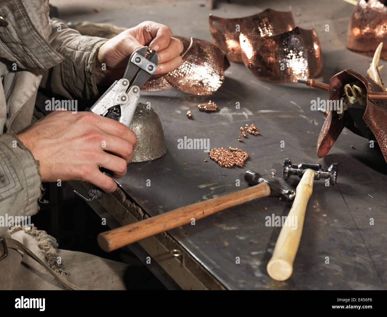 Image recadrée de forgerons mains travaillant avec des rivets de cuivre Photo Stock