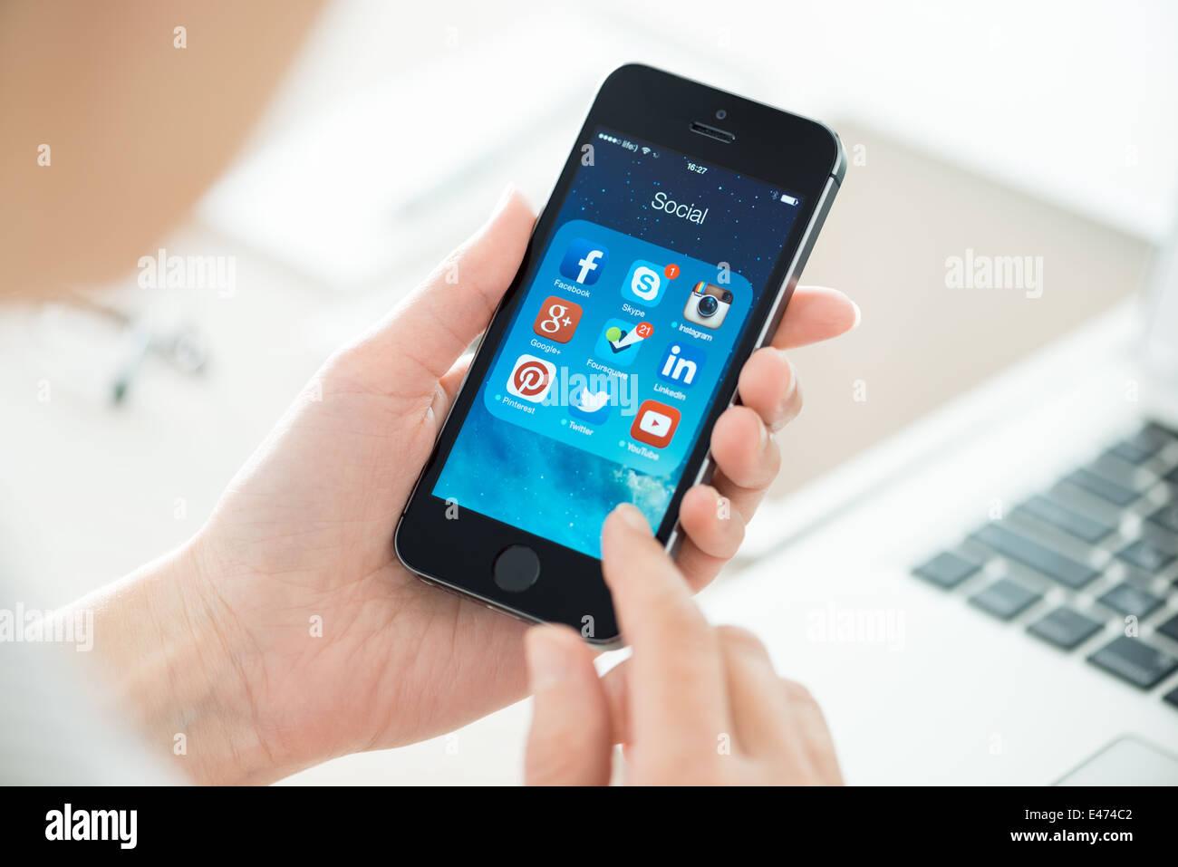 Femme à la recherche sur les applications de médias sociaux sur un tout nouveau Apple iPhone 5S noir Photo Stock