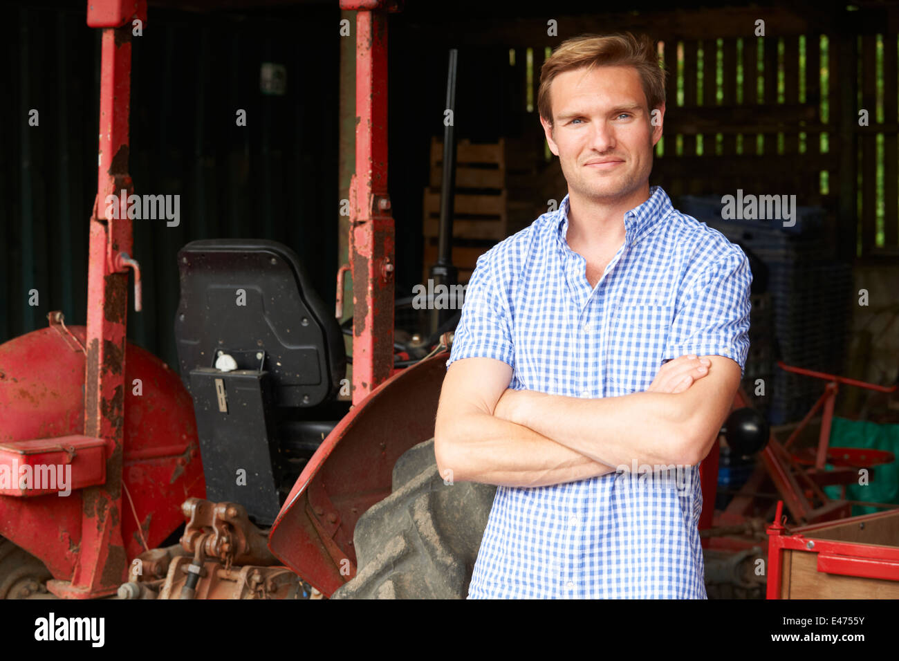 Farmer Standing Next to Old Fashioned Tracteur In Barn Photo Stock