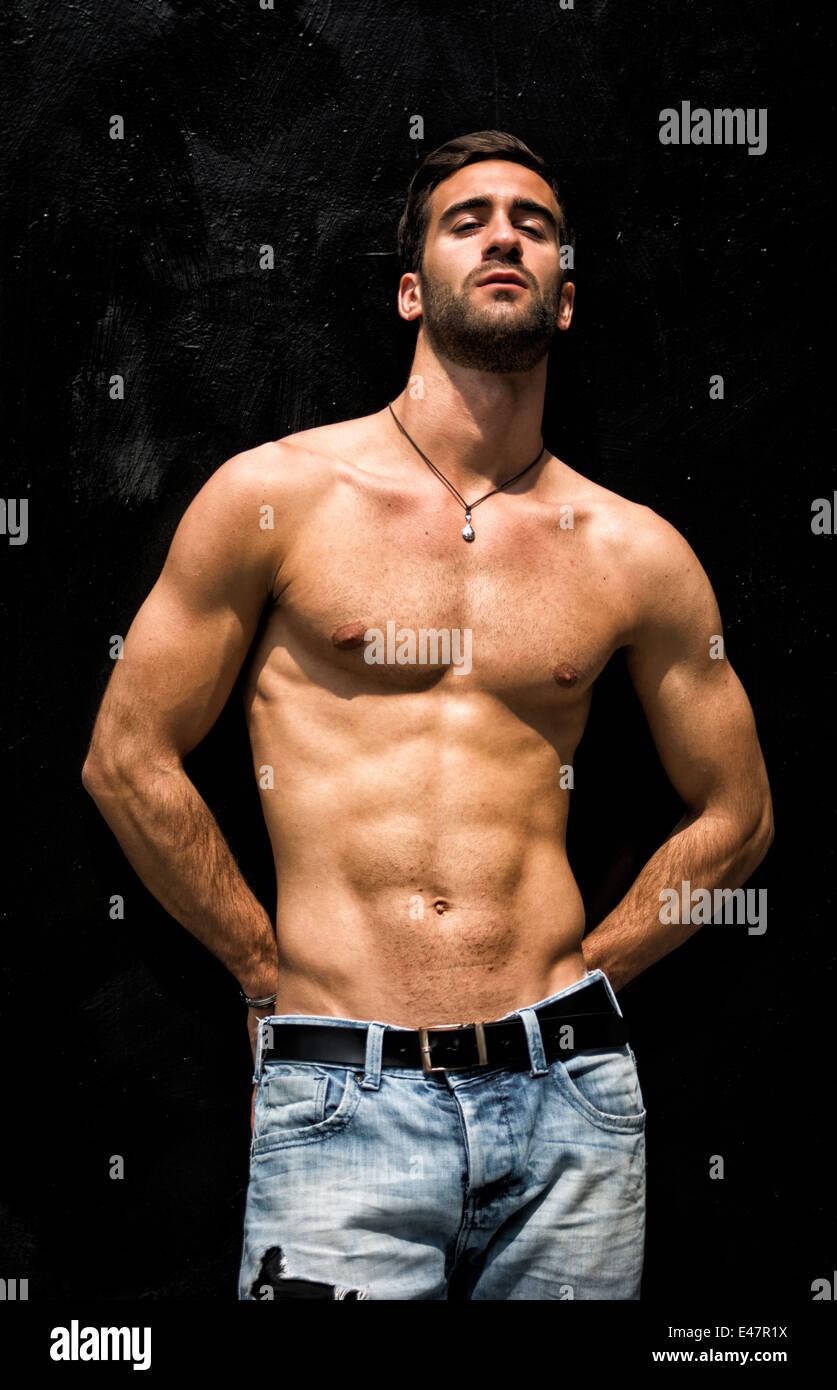 Homme Barbu Nu beau jeune homme barbu torse nu debout contre le mur noir, looking