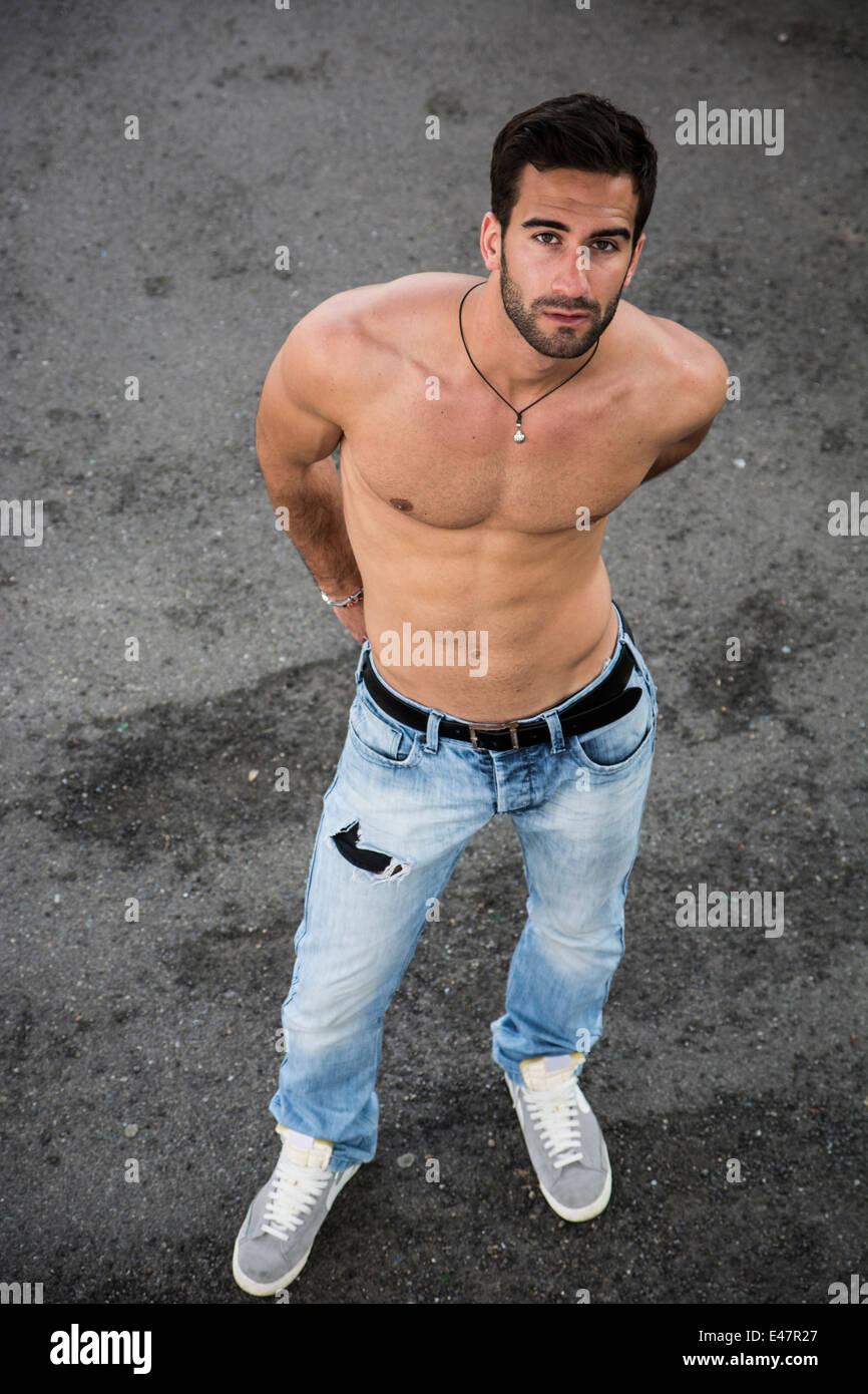 Homme Barbu Nu beau jeune homme barbu torse nu debout sur sol d'asphalte, looking
