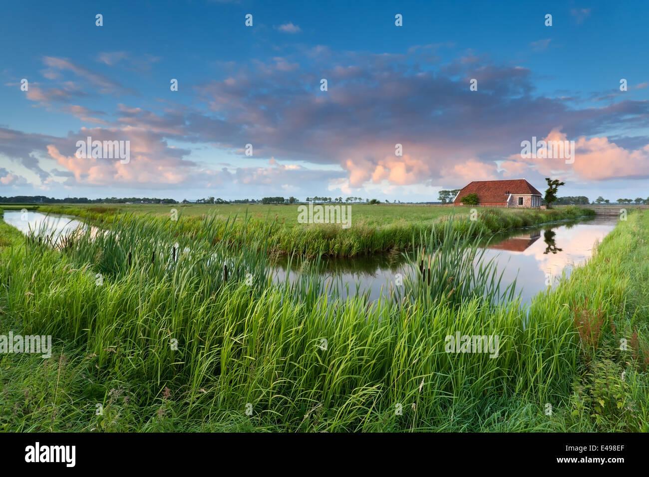 Charmante ferme par la rivière au coucher du soleil, Pays-Bas Photo Stock