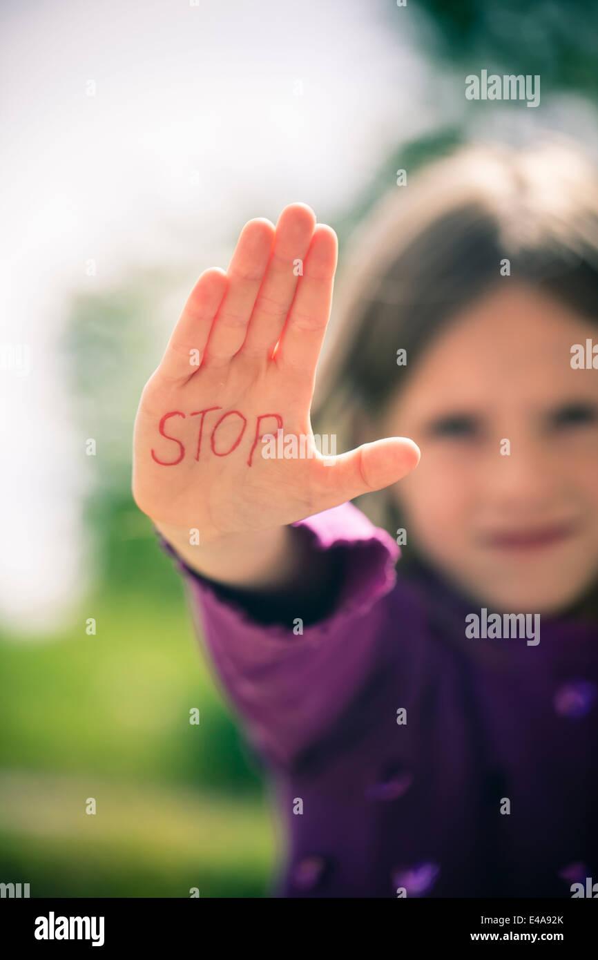 Petite fille montrant palm avec le mot STOP sur elle Photo Stock