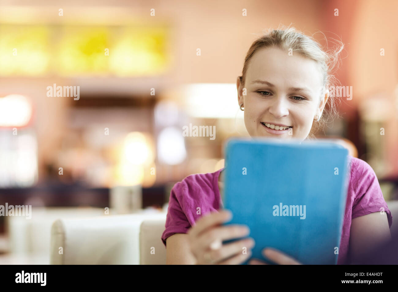 Young happy woman in cafe with tablet PC Photo Stock