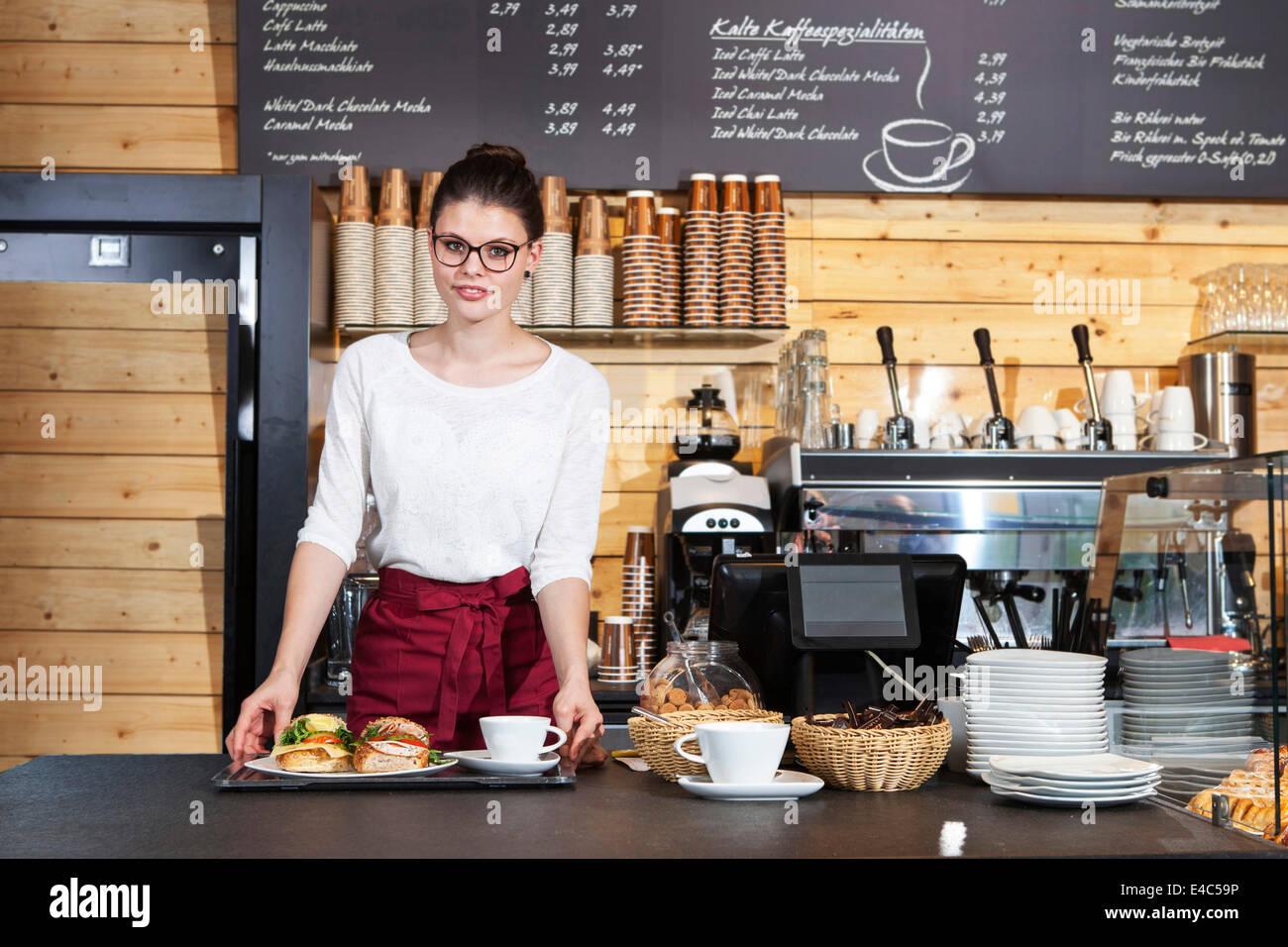 Serveuse dans un café servant des sandwiches dans un bac Photo Stock