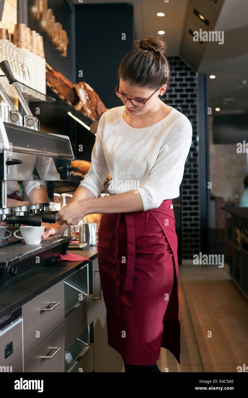 Serveuse dans un café à la machine à café de travail Photo Stock