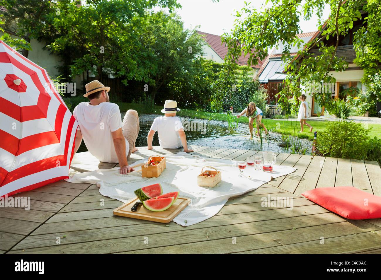 Imbéciles autour de la famille par l'étang, les projections d'eau, Munich, Bavière, Allemagne Photo Stock