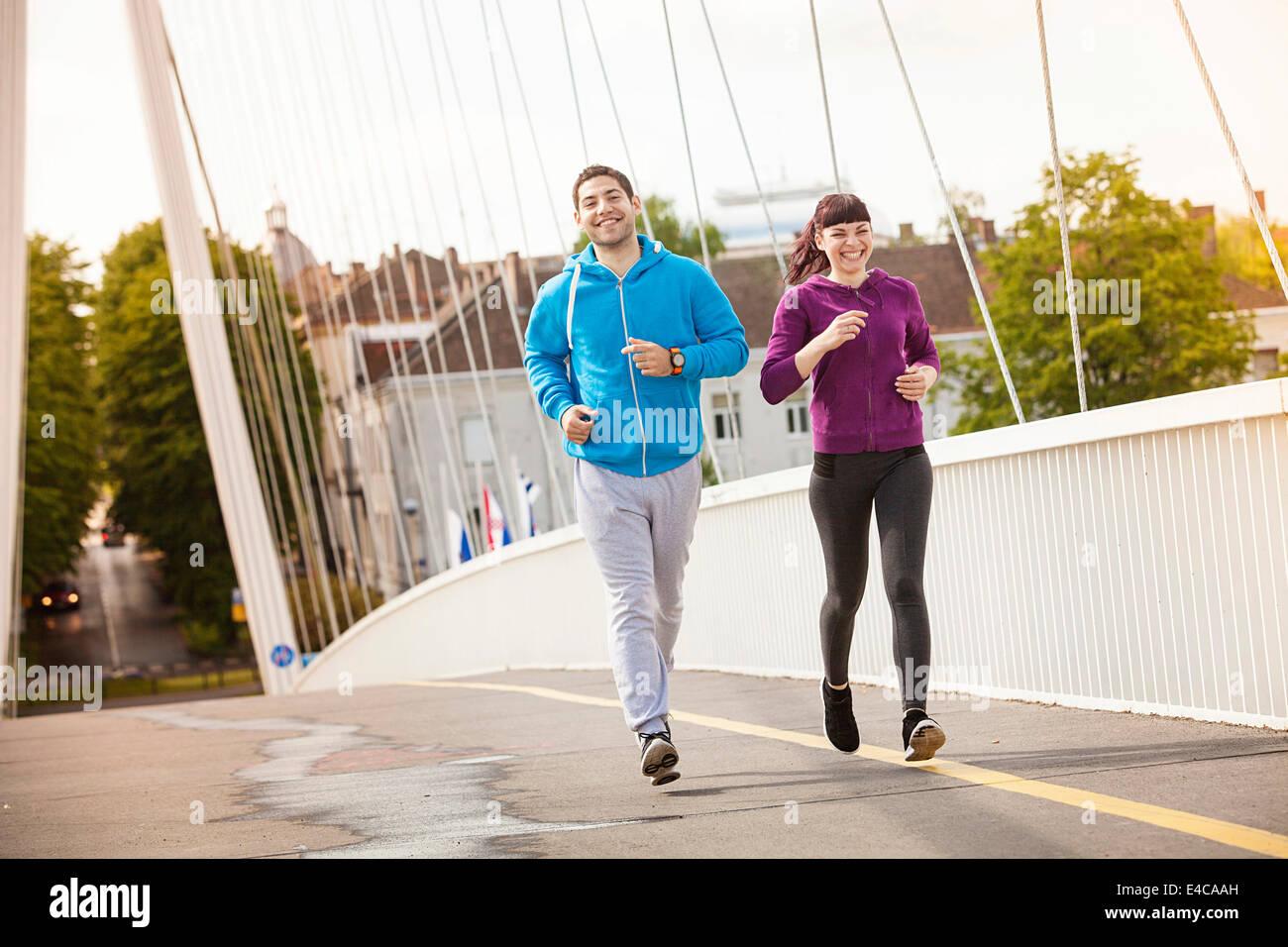 Jeune couple jogging sur le pont, Osijek, Croatie Photo Stock