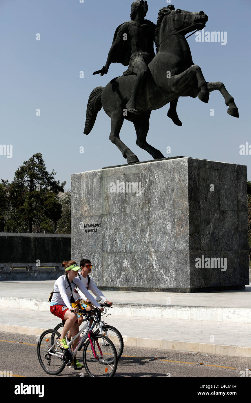 Un couple de la bicyclette en face d'Alexandre la grande statue à Thessalonique, Grèce Photo Stock