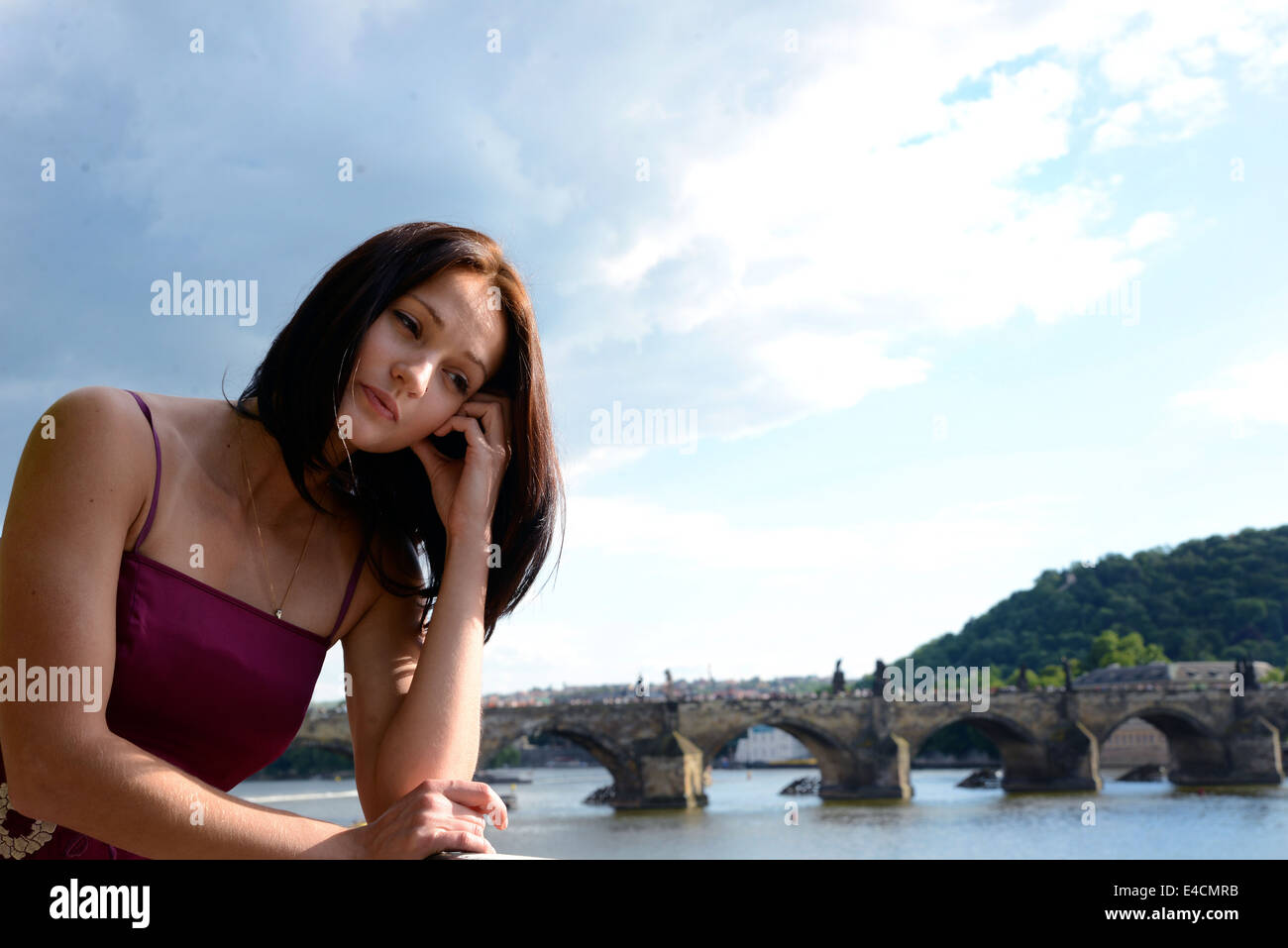 Belle Dame penser avec inquiétude en face d'un pont panoramique, rivière, montagne et ciel Photo Stock