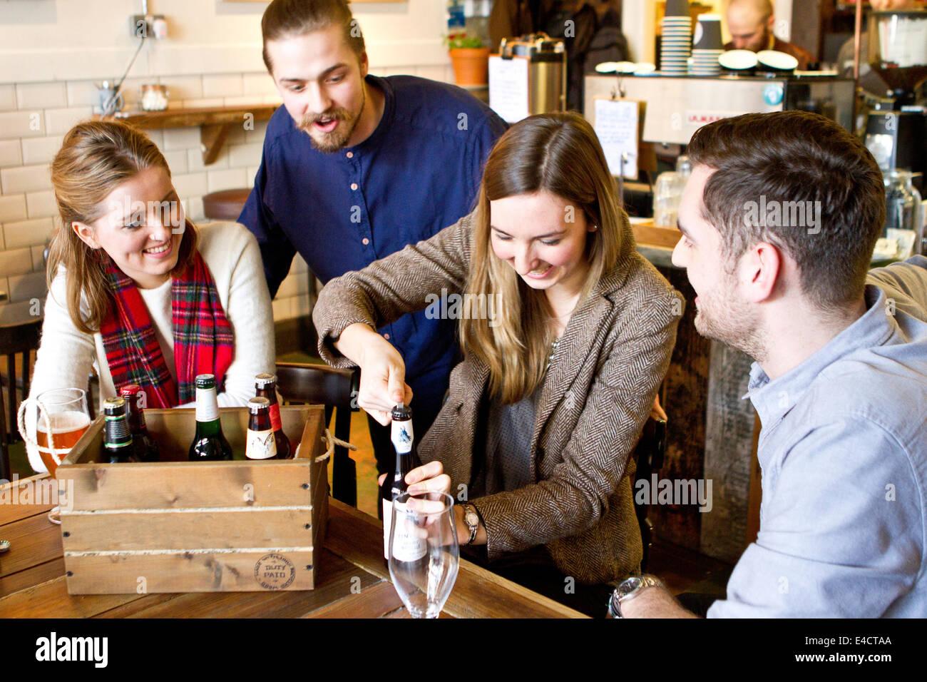 Jeune femme d'ouvrir une bouteille de bière, amis regardent, Dorset, Bournemouth, Angleterre Photo Stock