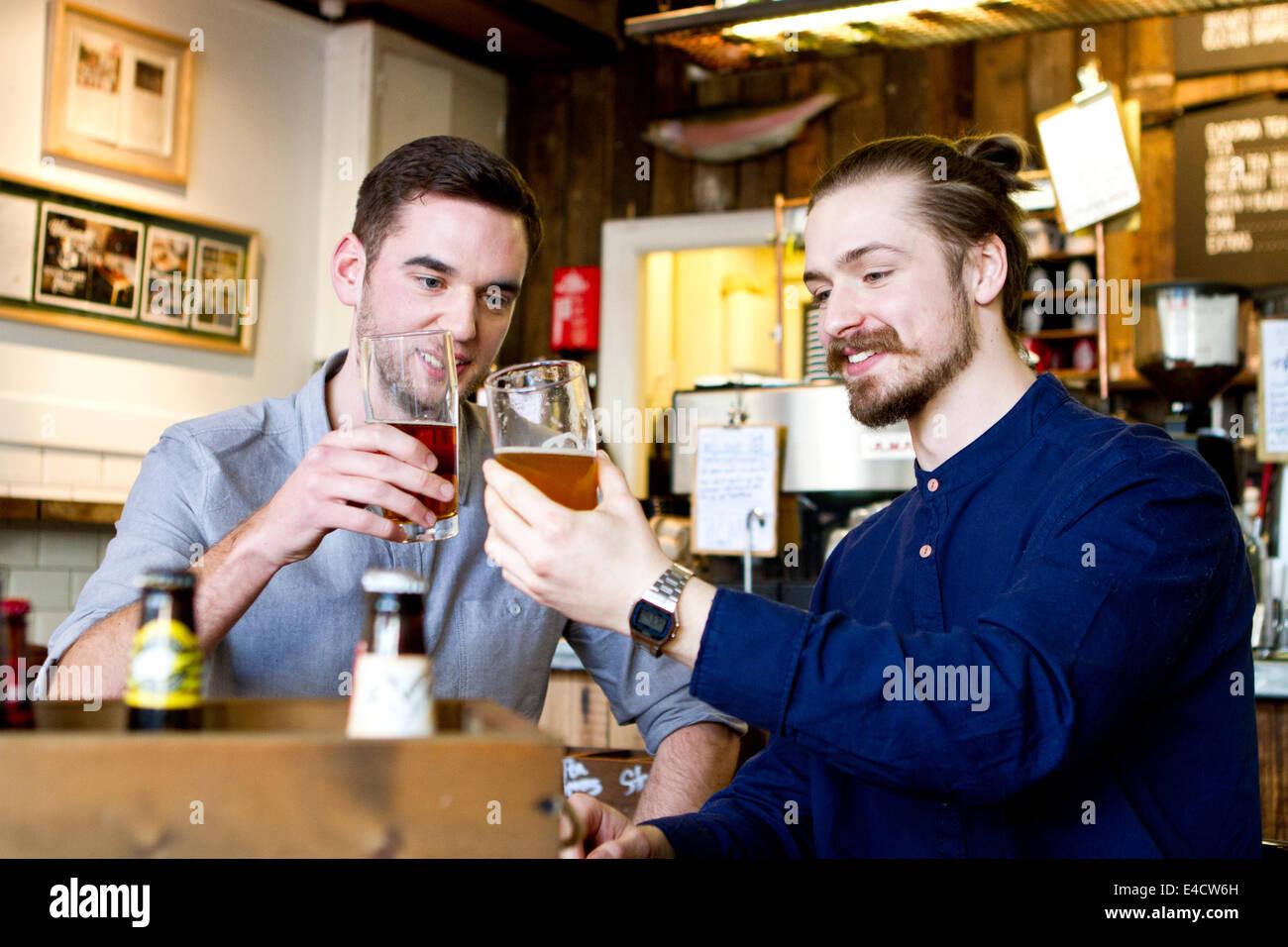 Young Men toasting avec de la bière dans un pub, Dorset, Bournemouth, Angleterre Photo Stock