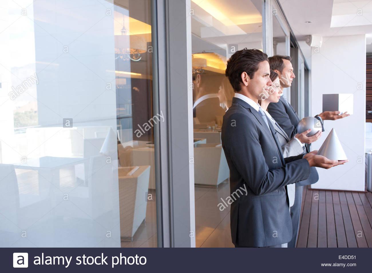 Les gens d'affaires détenant des figures géométriques Photo Stock