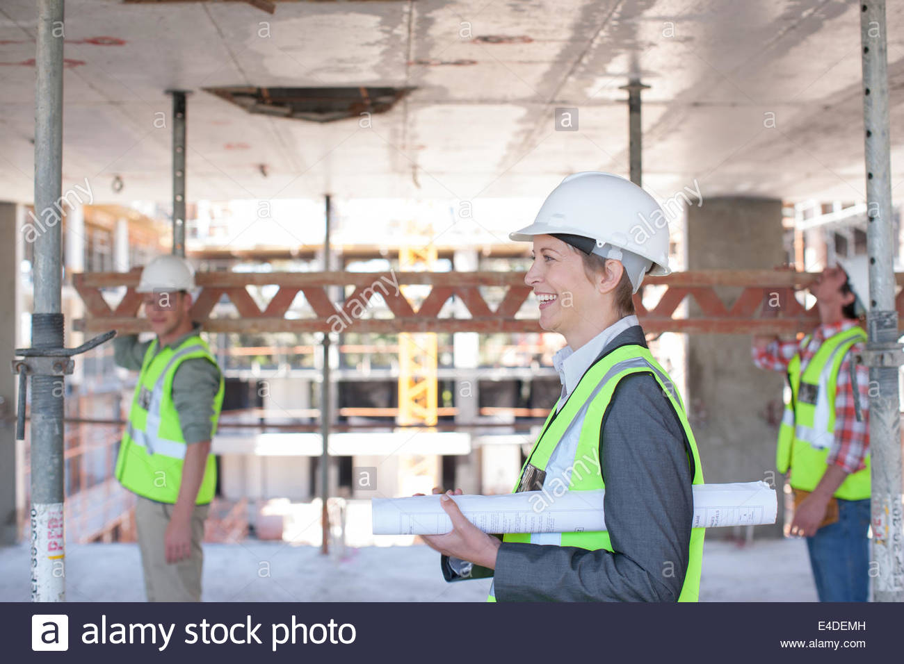 Construction Worker carrying blueprints on construction site Photo Stock