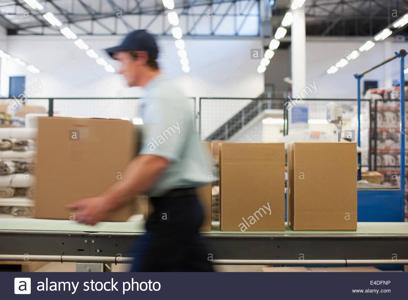 Worker carrying case dans la zone d'expédition Photo Stock