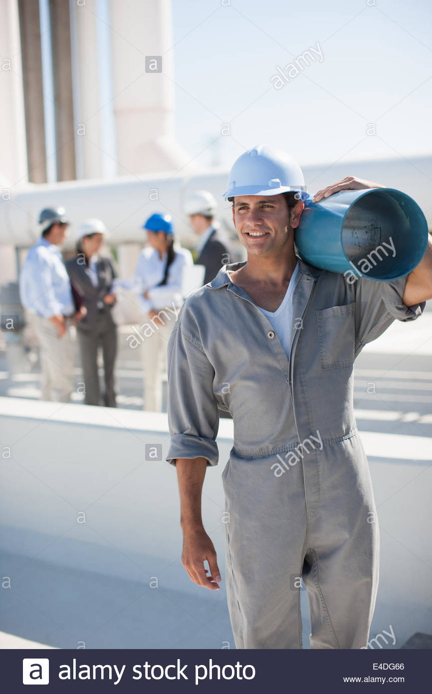 Worker in hard-hat carrying large pipe outdoors Photo Stock