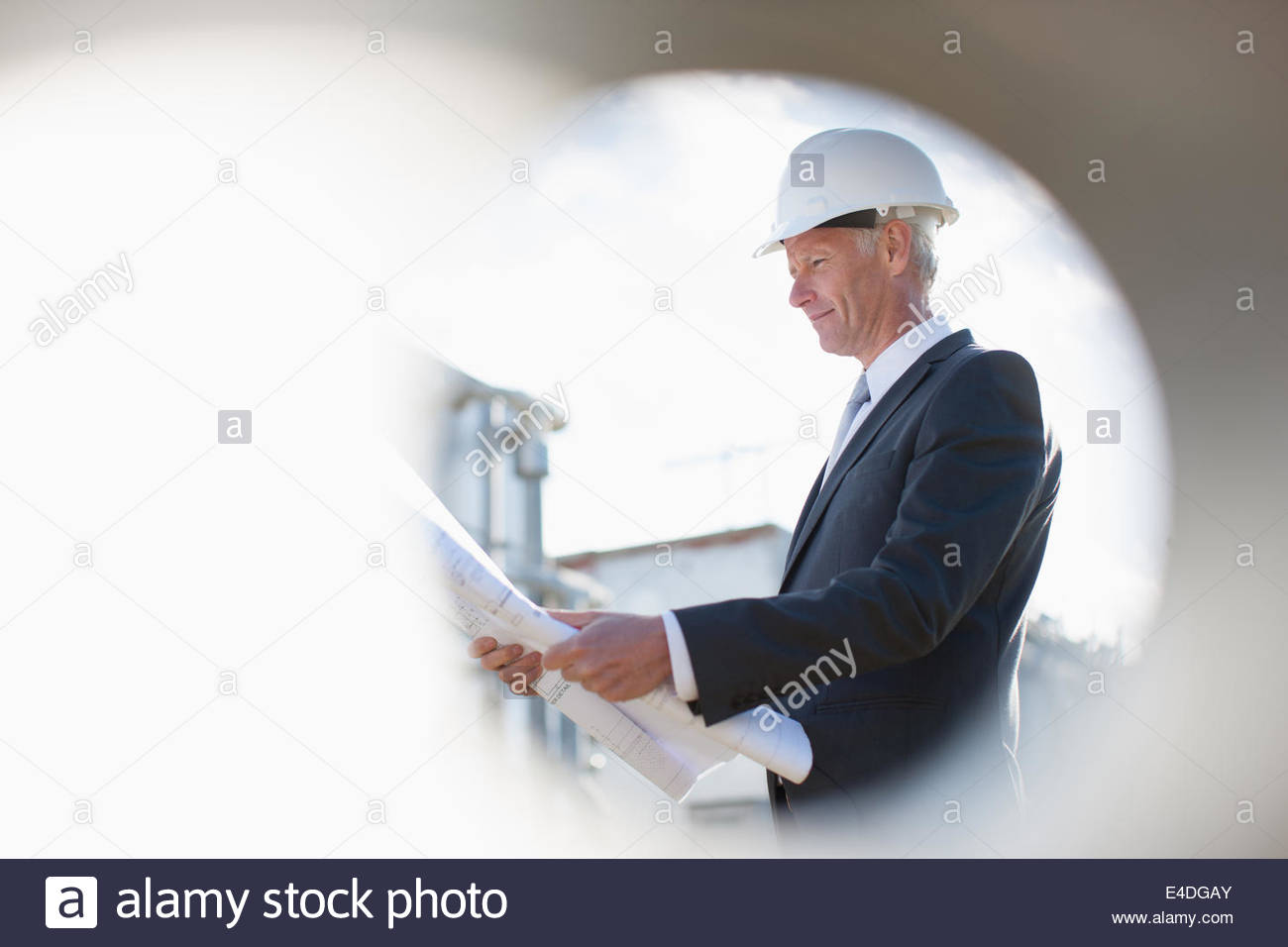 Businessman in hard-hat reviewing blueprints outdoors Photo Stock
