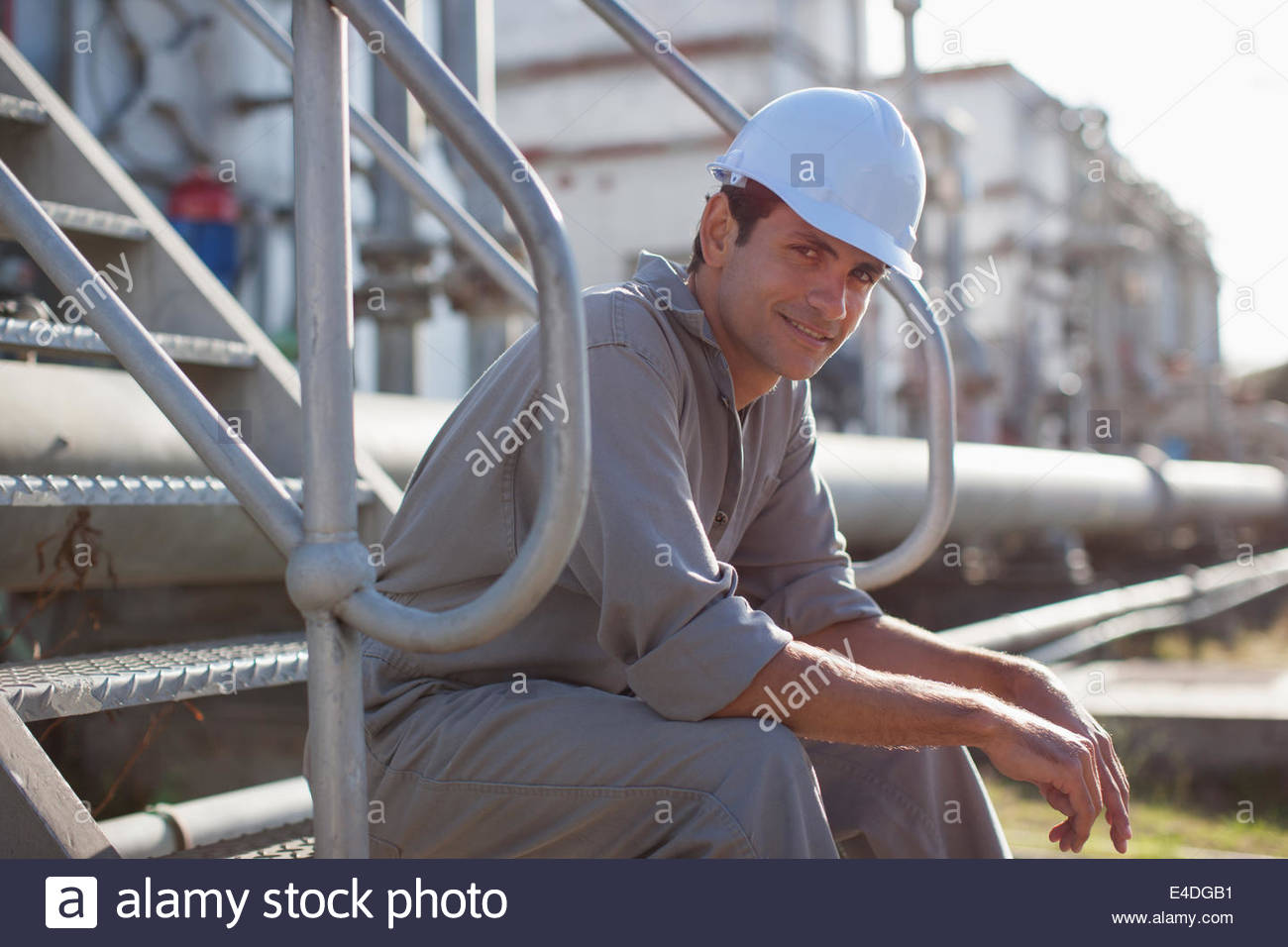 Worker in hard-hat assis dans les marches Photo Stock