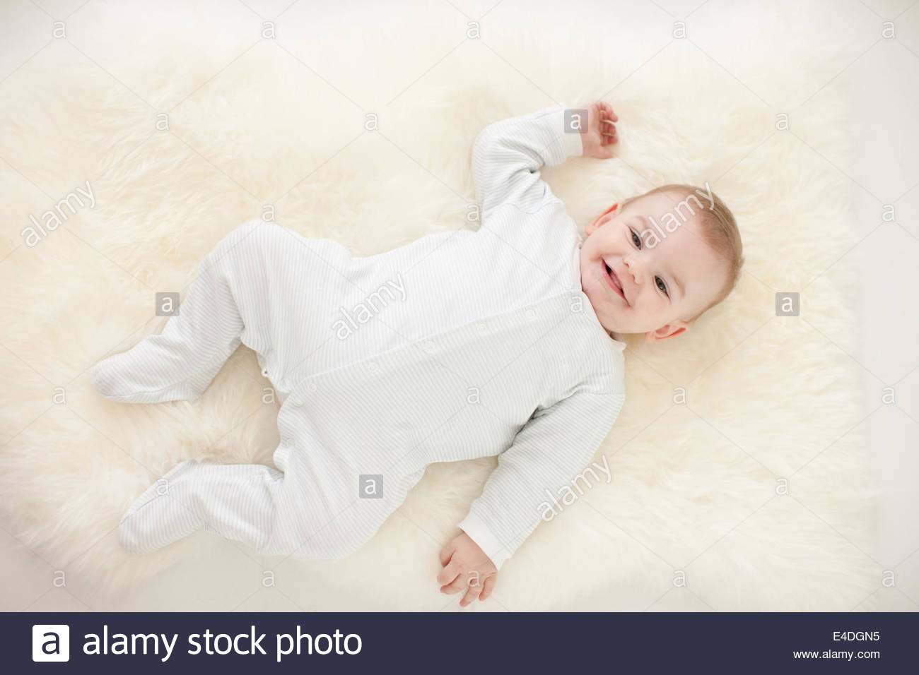 Smiling baby laying on rug Photo Stock