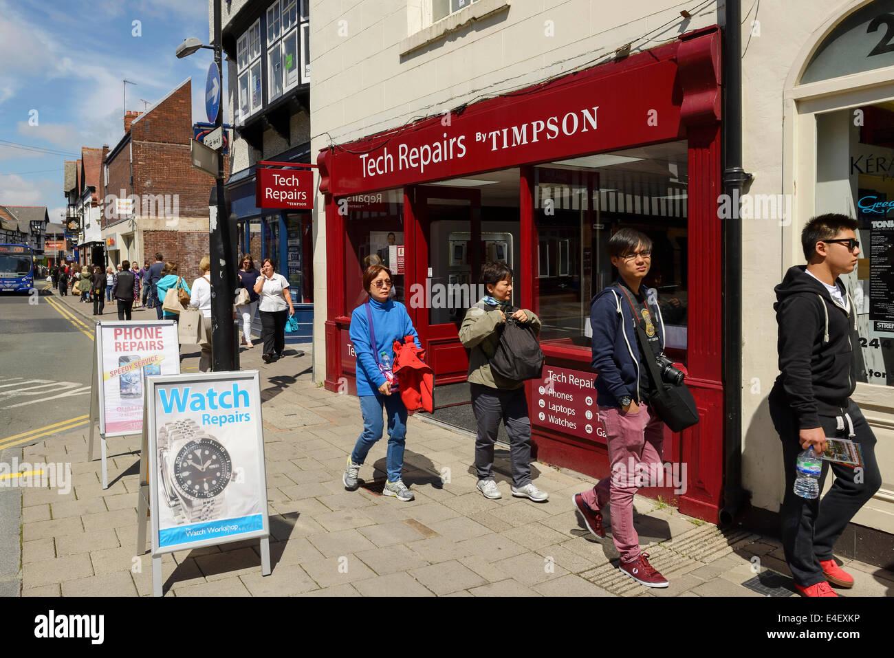 Des gens devant un magasin de réparations Tech Timpson Photo Stock