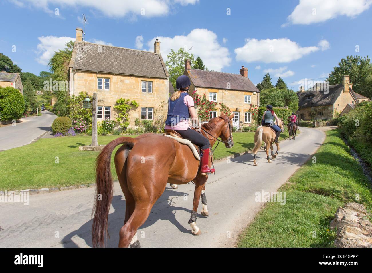 L'équitation dans le village de Cotswold Stanton, Gloucestershire, England, UK Photo Stock
