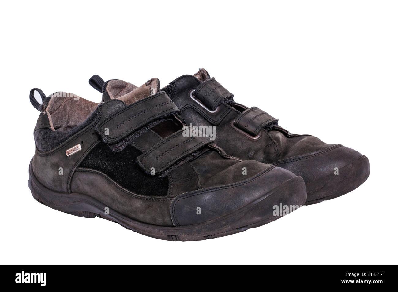 Une paire de garçons velcro noir usé fixer chaussures école sur un fond blanc Photo Stock