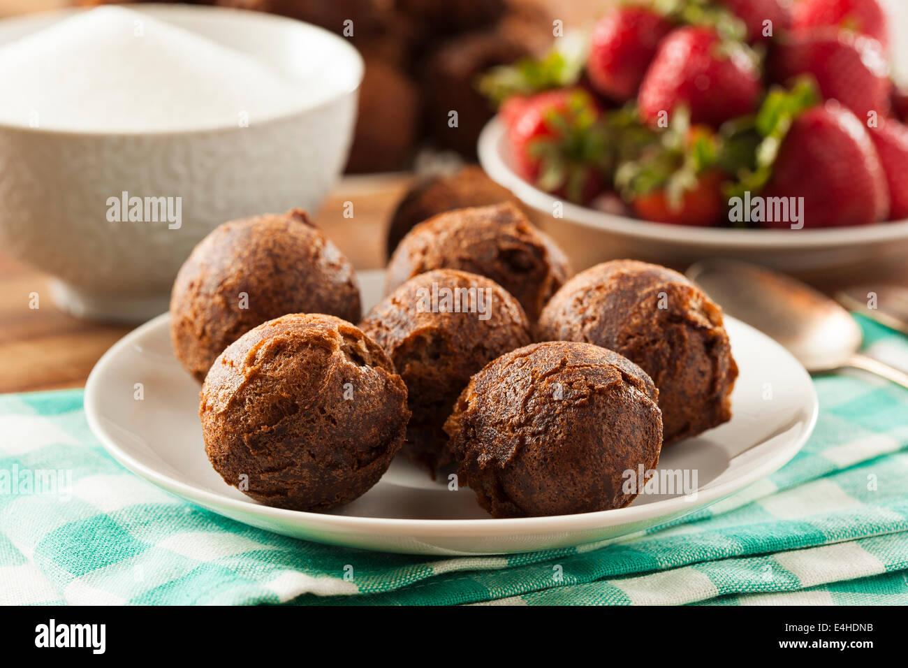 Les trous de beignes au chocolat maison avec du sucre pour le petit déjeuner Photo Stock