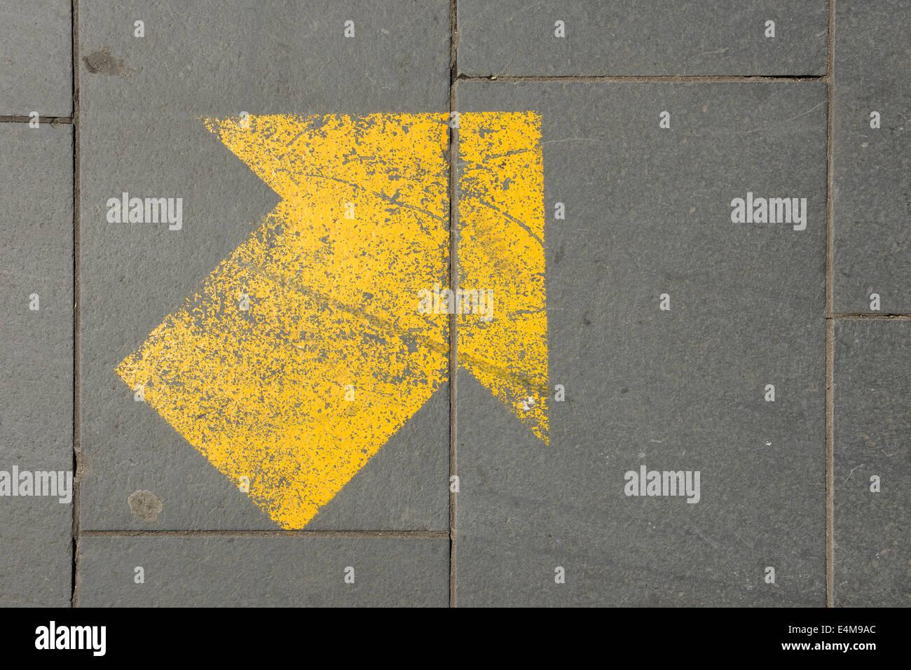 La forme de flèche peint sur la chaussée Photo Stock