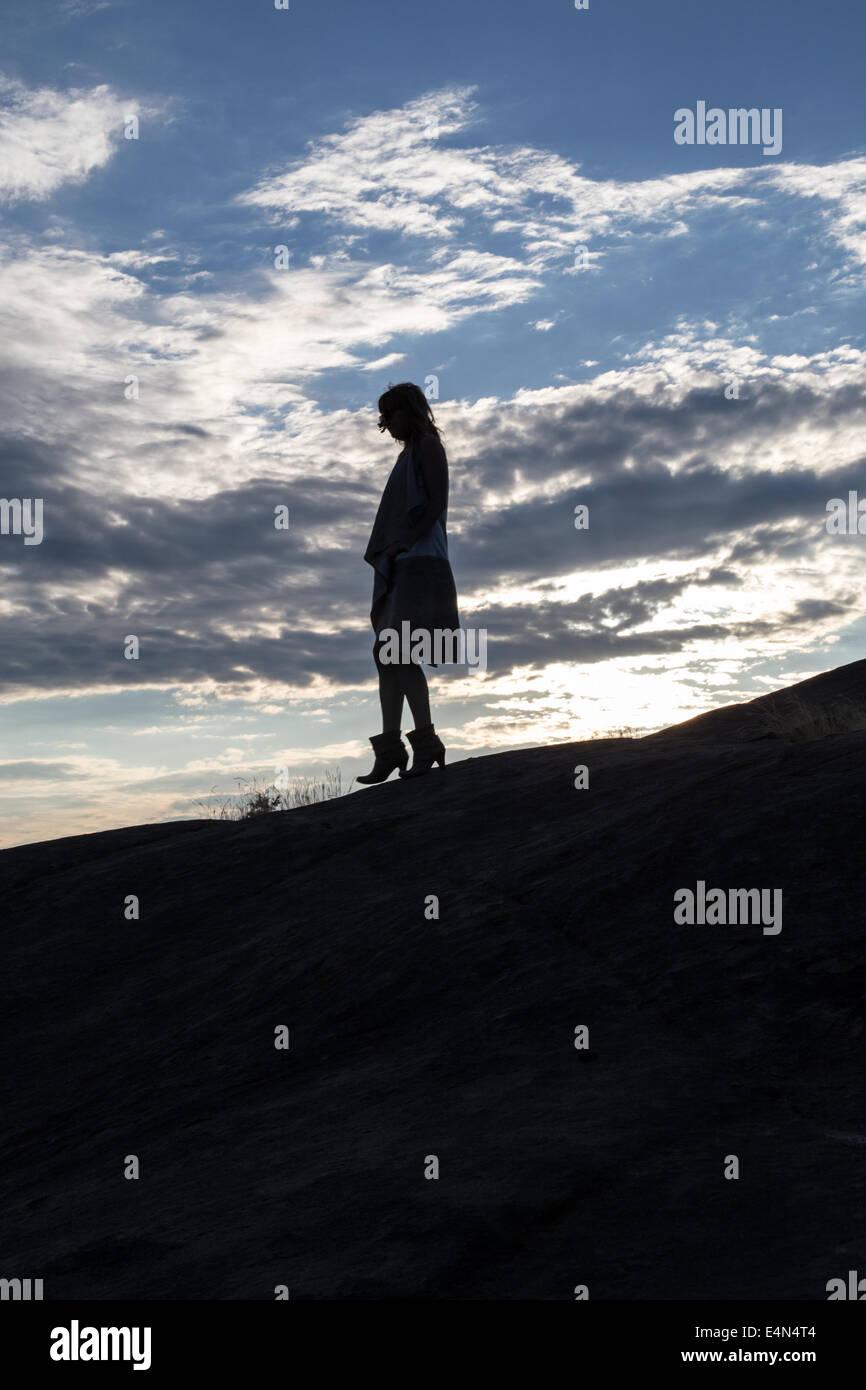 Silhouette d'une femme perdue au coucher du soleil dans une robe tenant un sac avec des nuages dans l'arrière Photo Stock