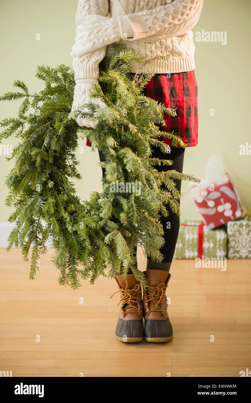 La section basse de woman holding christmas wreath Photo Stock