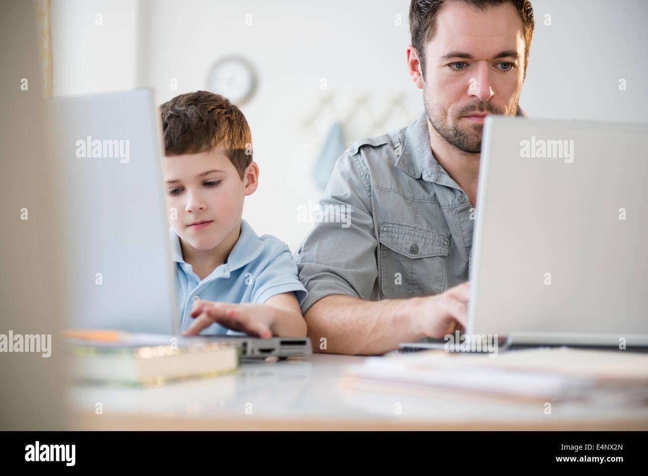 Père et fils (8-9) travaillant sur des ordinateurs portables Photo Stock