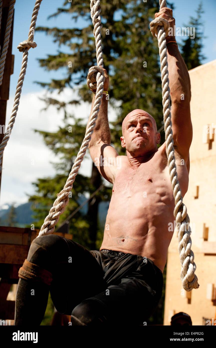 Un homme sur un obstacle au Whistler Vancouver Tough Mudder événement. Photo Stock