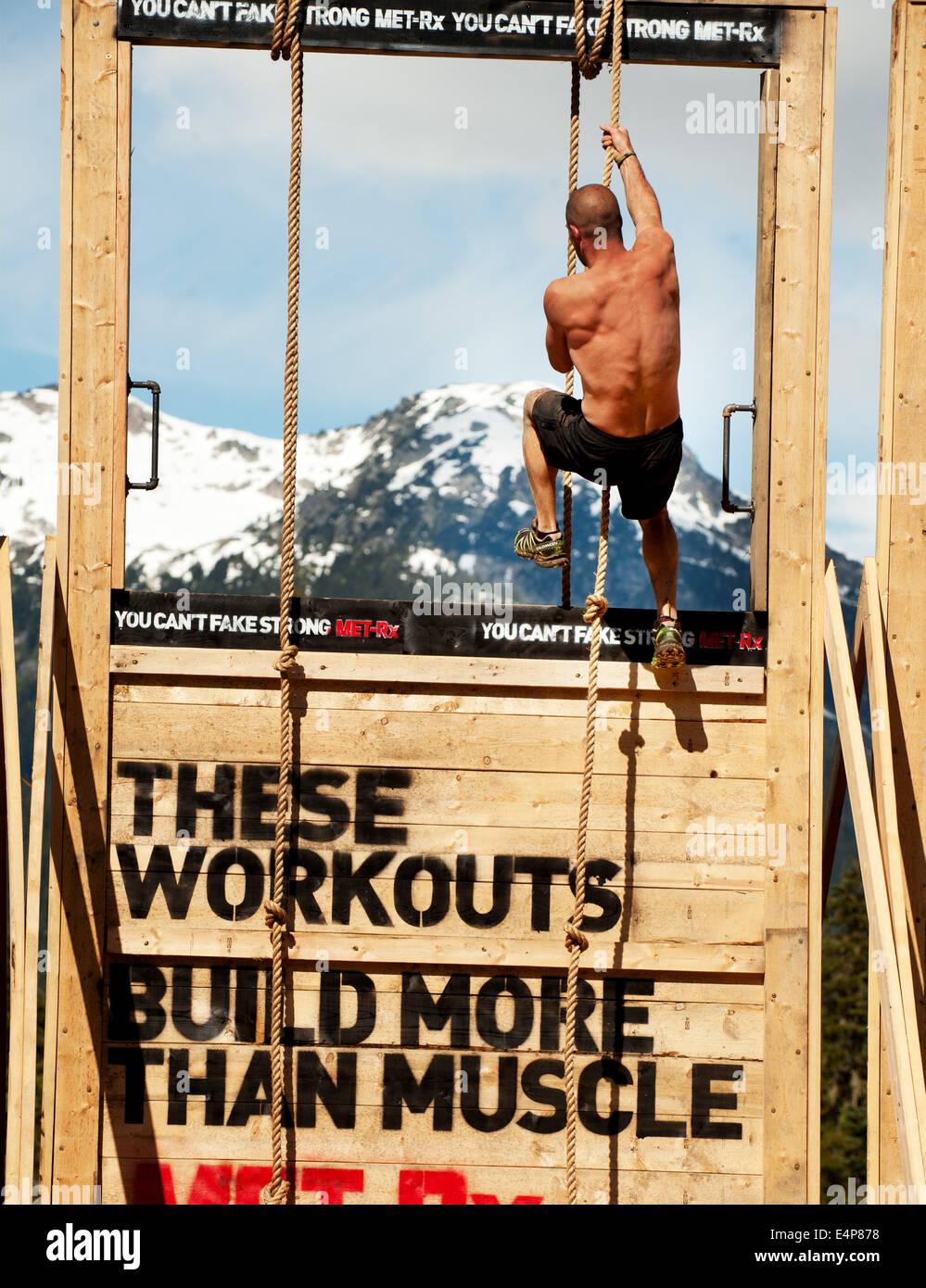 Un homme grimpe un mur au Whistler Vancouver Tough Mudder événement. Photo Stock
