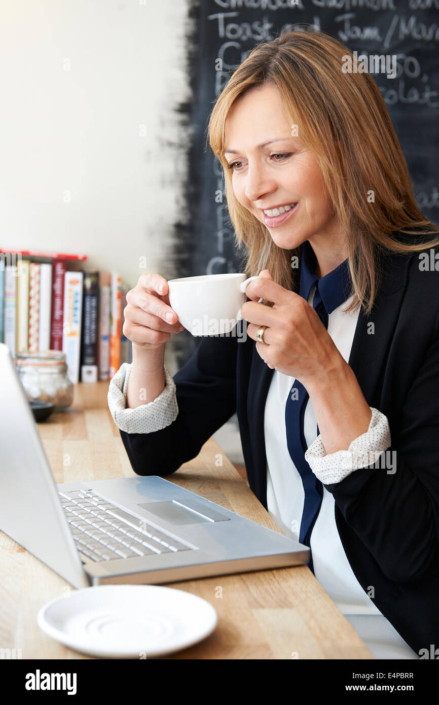 Businesswoman Using Laptop In Cafe Photo Stock