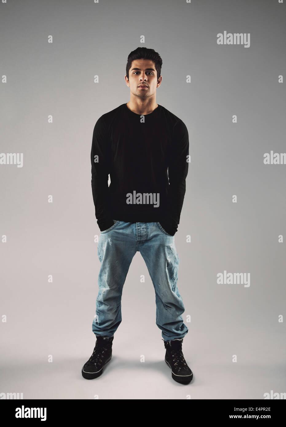 Portrait de jeune homme élégant dans les occasionnels debout avec ses mains dans la poche sur fond gris. Photo Stock