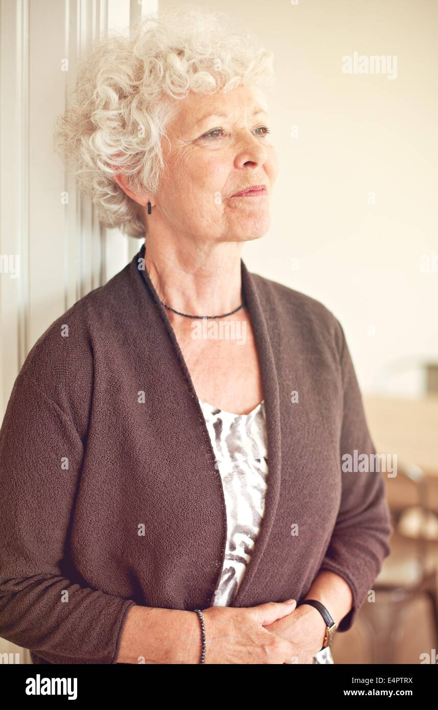 Senior woman looking away et penser à quelque chose Photo Stock