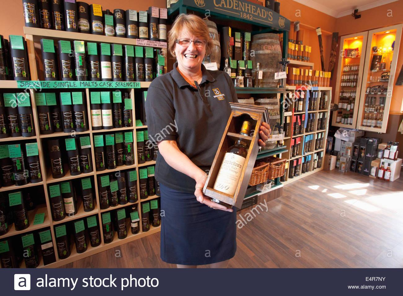 Le vendeur pose pour une photo avec une bouteille de whisky single malt 1919 évalué à 50 000 livres Photo Stock