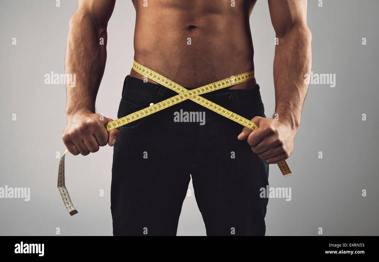 La mesure de l'homme remise en forme son corps. Recadrées et la mi-section image de jeune homme de mesurer Photo Stock