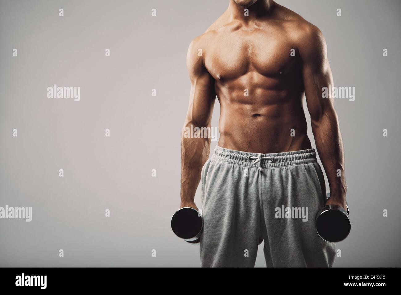 Portrait d'un modèle masculin en pantacourts holding haltères en deux mains sur fond gris avec copie Photo Stock