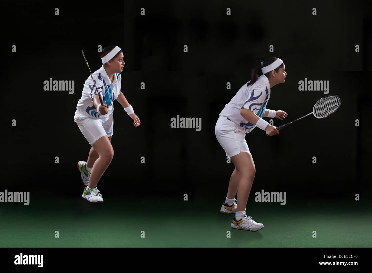 Photo de profil joueurs de jouer double badminton sur fond noir Photo Stock
