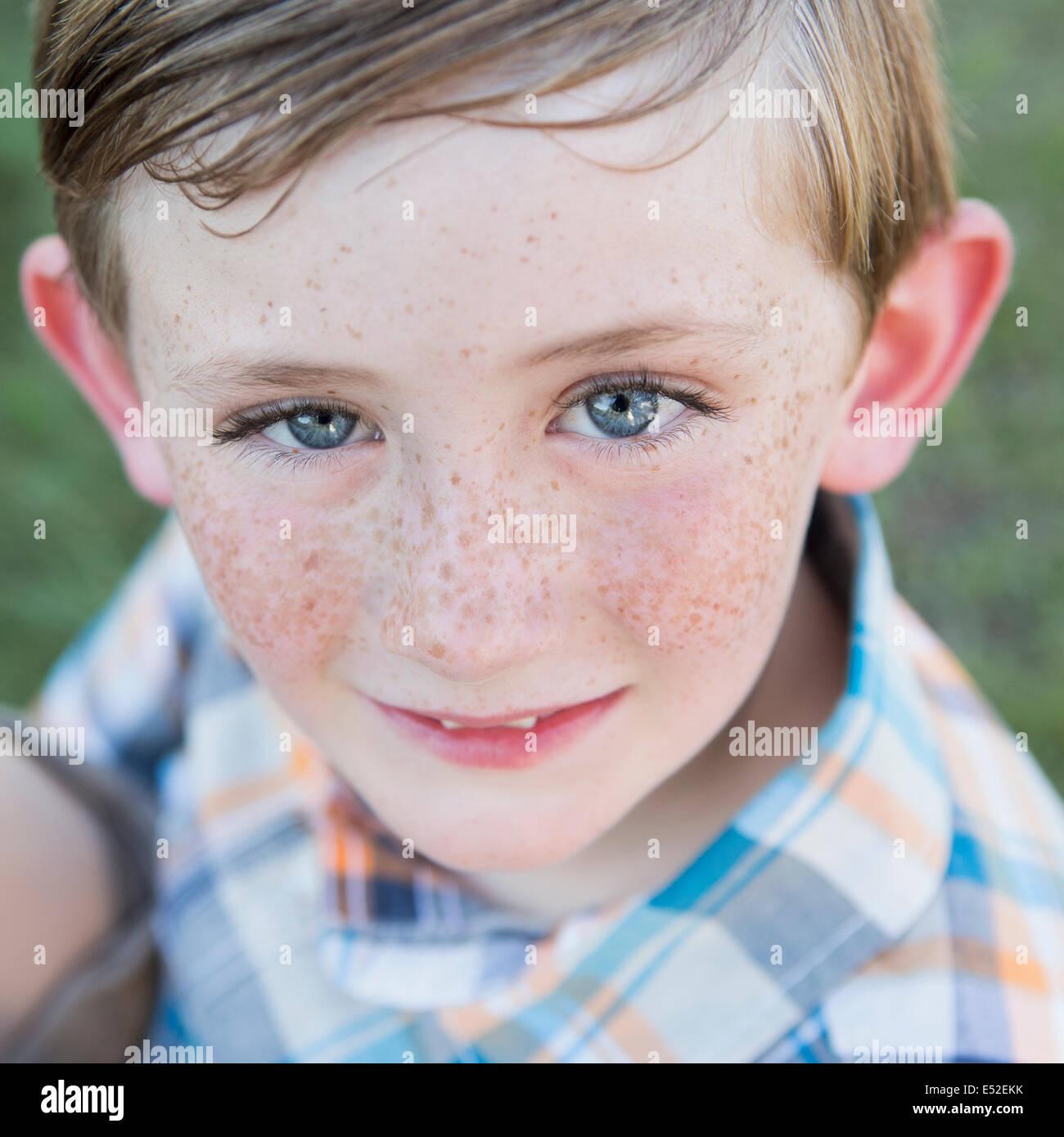 Portrait d'un jeune garçon avec des yeux bleus et des taches de rousseur sur son nez. Photo Stock