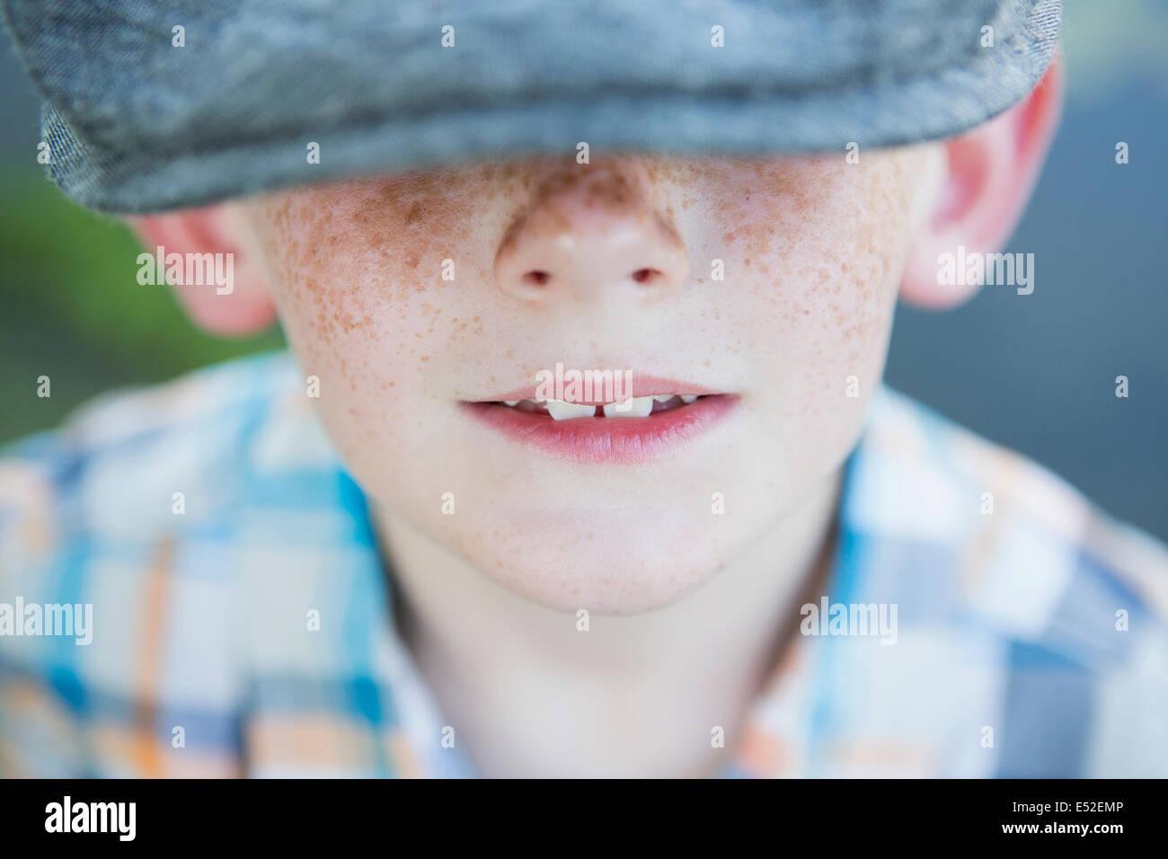 Un jeune garçon avec un nez de rousseur, portant un chapeau avec un large bord. Photo Stock