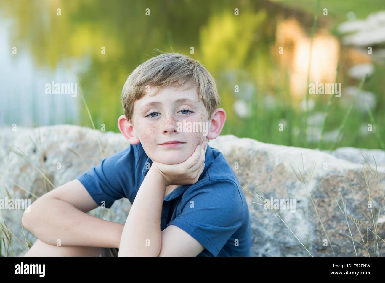 Head and shoulders portrait d'un jeune garçon assis avec son menton reposant sur sa main. Photo Stock
