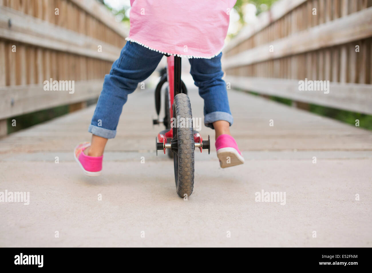 Un enfant à cheval sur un vélo sur un trottoir. Photo Stock