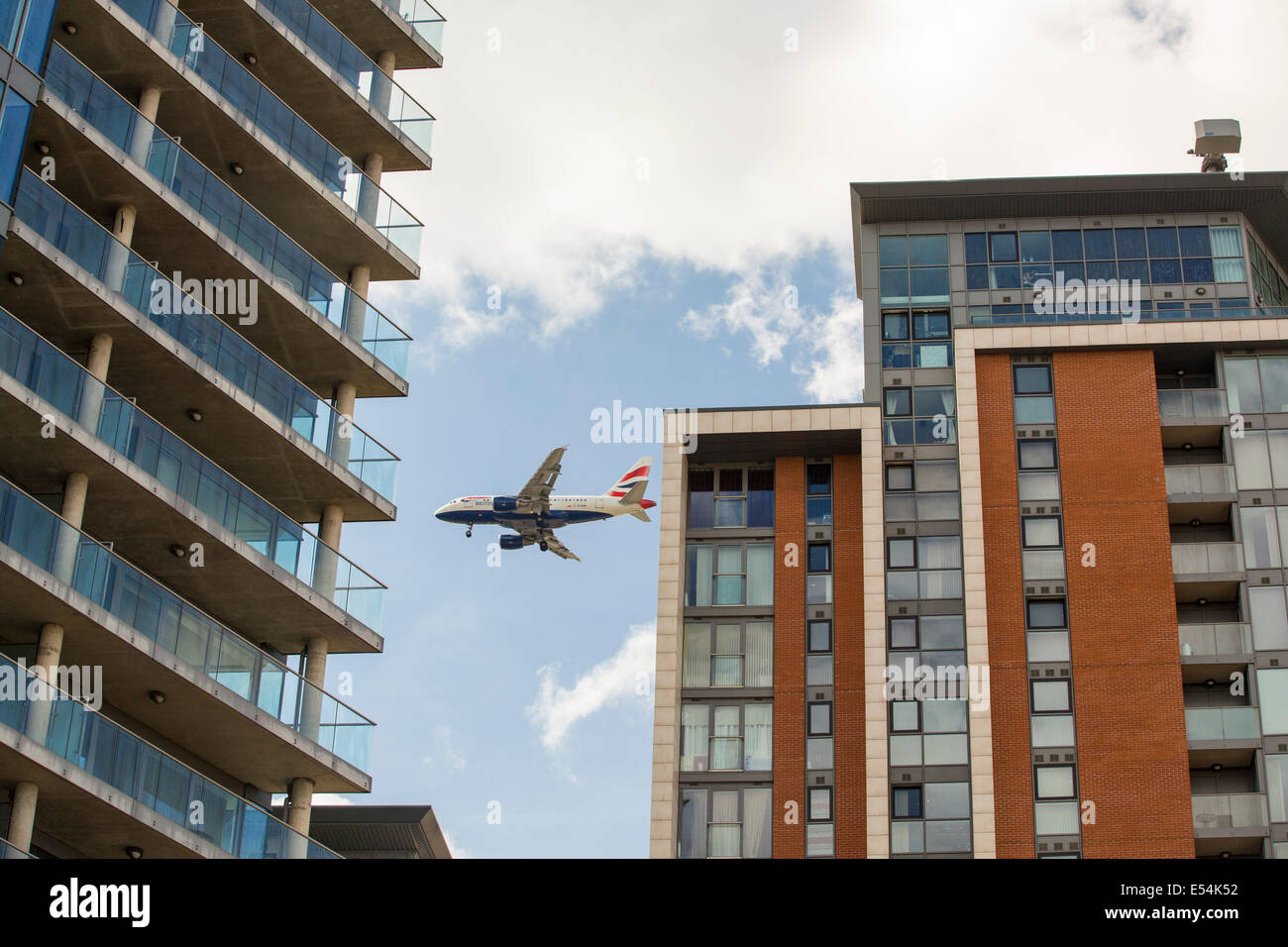 Un avion battant vacances passé les blocs comme il arrive en terre à City Airport, London, UK. Photo Stock