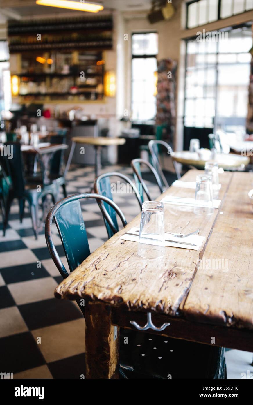 Table communautaire avec des chaises en métal et marbre à damier en restaurant industrielle moderne. Photo Stock