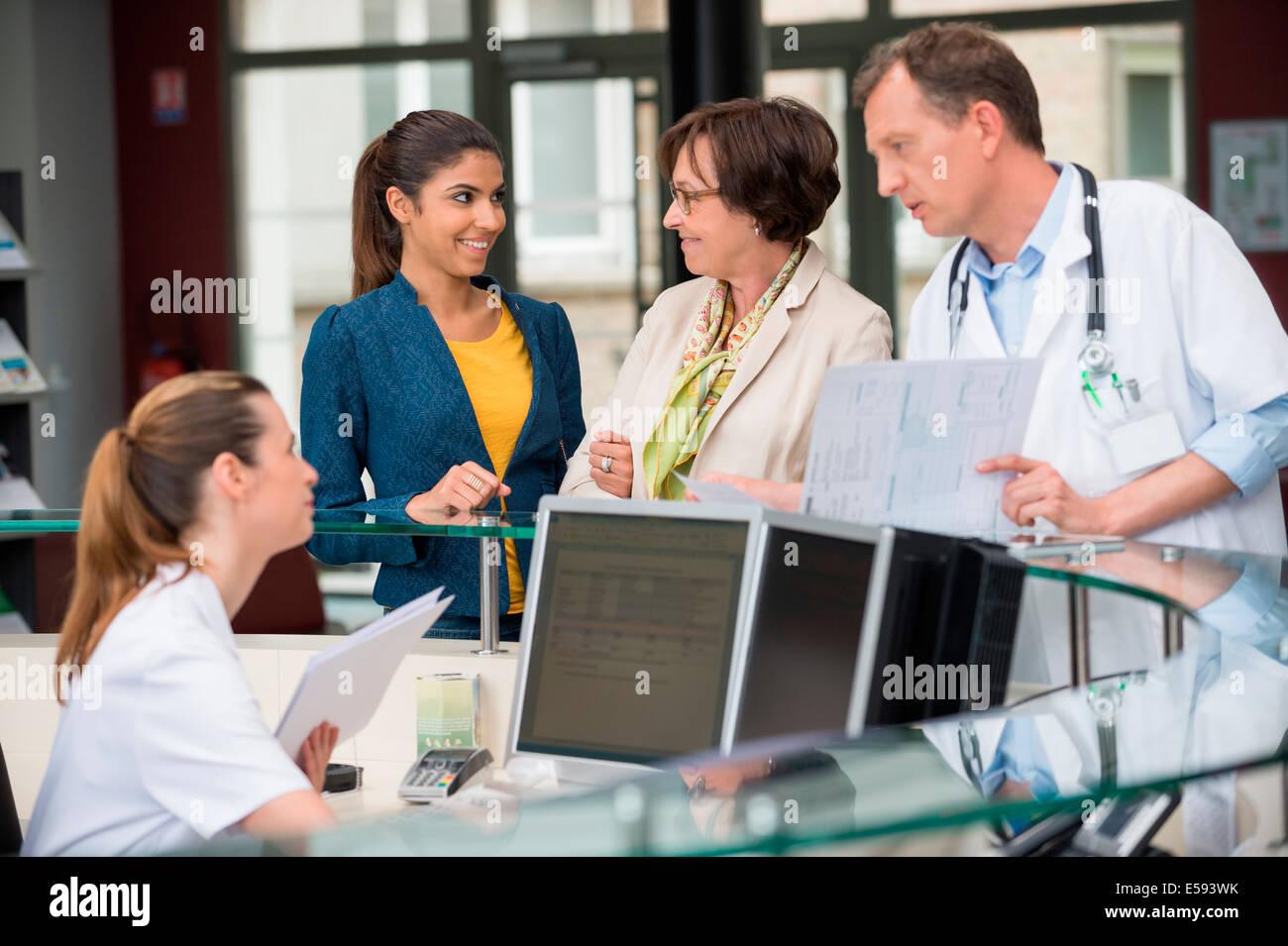 Médecin homme discutant avec réceptionniste au bureau de réception