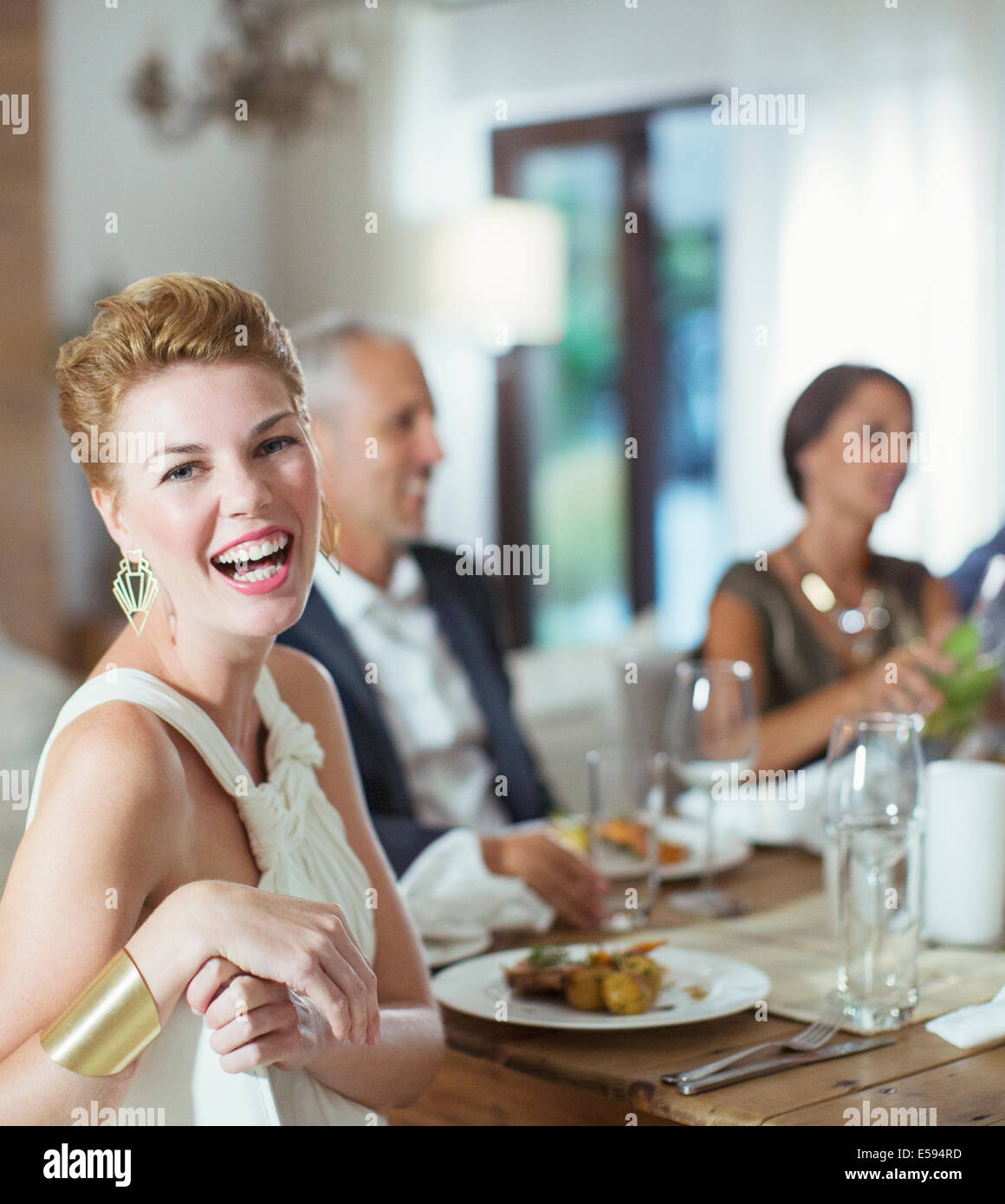 Woman laughing at dinner party Banque D'Images
